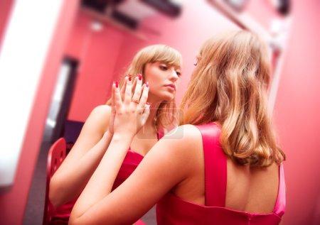 Photo pour Beauté de la femme. jeune femme devant le miroir dans la salle de maquillage. - image libre de droit