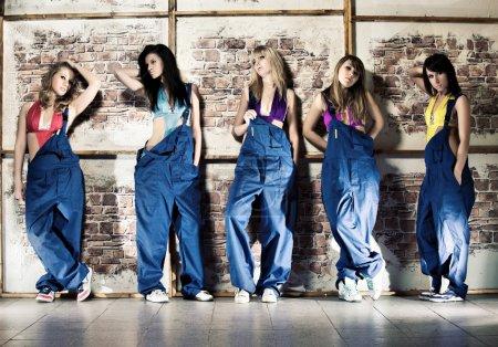 Foto de Equipo de trabajo de mujeres. cinco mujeres jóvenes sobre fondo de pared. - Imagen libre de derechos