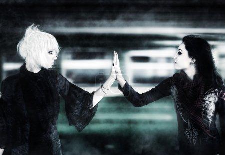 Two goth women touching hands