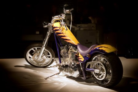 Photo pour Chopper moto dans un spot de lumière à l'exposition . - image libre de droit