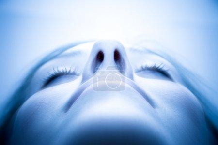 Photo pour Délicieux visage de femme. Teinte bleue, mise au point douce et brillance spéciale au-dessus du visage . - image libre de droit