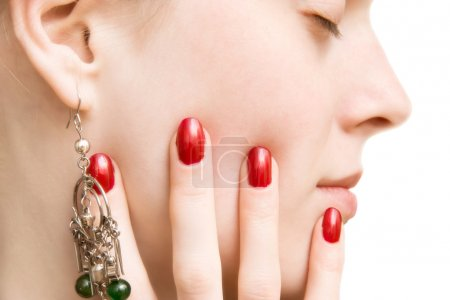 Young woman face and hand with red nails