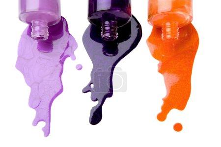 Photo pour Le vernis à ongles de couleur qui est déversant de bouteilles sur un fond blanc - image libre de droit