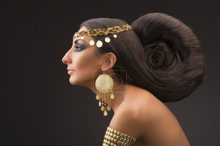 Photo pour Portrait de la jeune femme dans un profil dans le style du sud-est avec une belle coiffure et ornements d'or sur fond noir. - image libre de droit