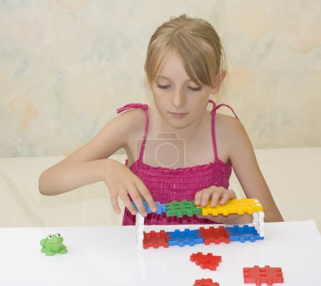 Little girl build construction from the