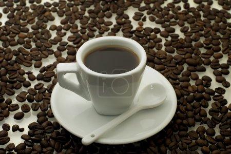 Photo pour Tasse blanche avec un café sur un fond de café en grains - image libre de droit
