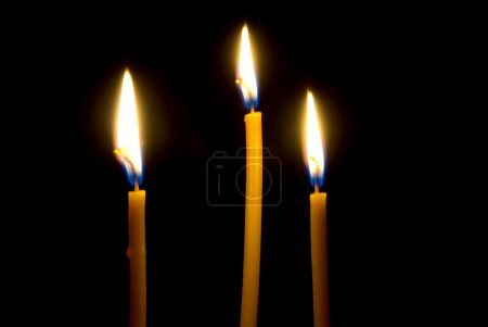 Photo for Three burning, church, waxy candles, close-up illuminate the darkness, before itself. - Royalty Free Image