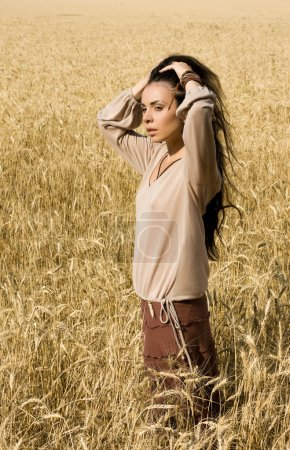 Attractive girl standing in wheat field