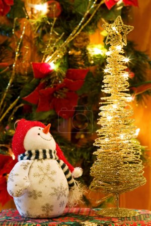 Photo for Celebrating the magic of Christmas with Snowman and golden tree decorations. - Royalty Free Image