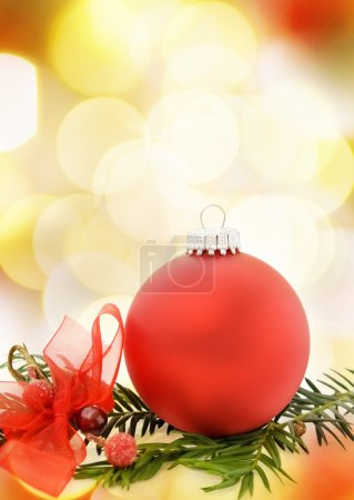 Photo for Christmas festive card with red bauble, ribbons and pine tree branch. Over defocused lights. - Royalty Free Image