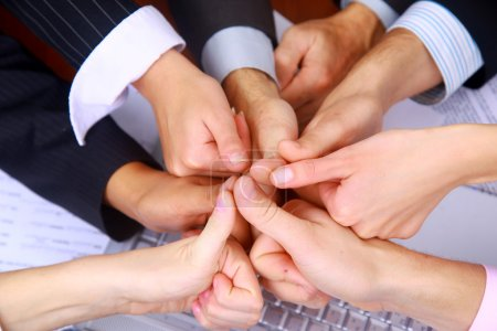 Photo for Group of business making a pile of hands in a light and modern office environment - Royalty Free Image