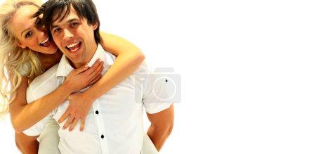 Happy young female enjoying a piggyback ride on boyfriends back against whi