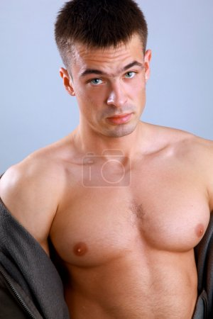 Young happy muscular man isolated on a blue background
