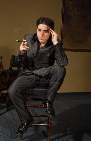 Gangster smokes cigar in retro bar