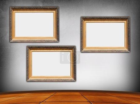 Three blank vintage frames in an rmpty room...