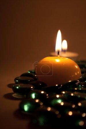 Photo pour Brûler des bougies sur des pierres de verre décoratives - image libre de droit