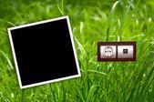 Energii zásuvky v trávě s prázdný rám