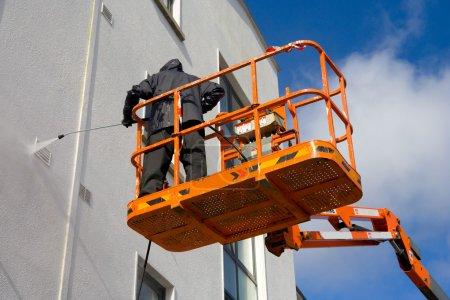 Photo pour Ouvrier dans Cherry-picker Laver un mur de bâtiment avec dispositif à haute pression - image libre de droit