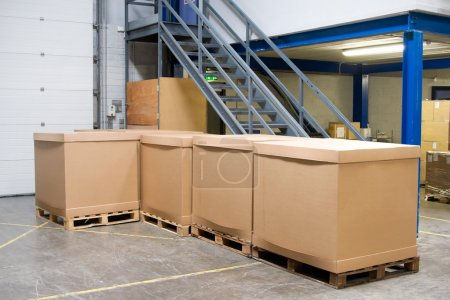 Photo for Pallets with cardboard cartons in industrial warehouse interior - Royalty Free Image