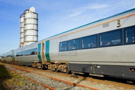 Photo pour Train de voyageurs et réservoirs de carburant en arrière-plan - image libre de droit
