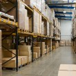 Industrial warehouse interior with shelves and pal...