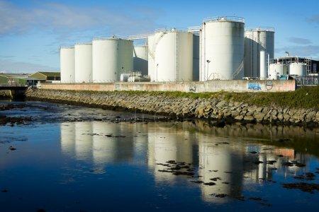 Photo pour Réservoirs de carburant sur le site industriel au bord de la rivière - image libre de droit