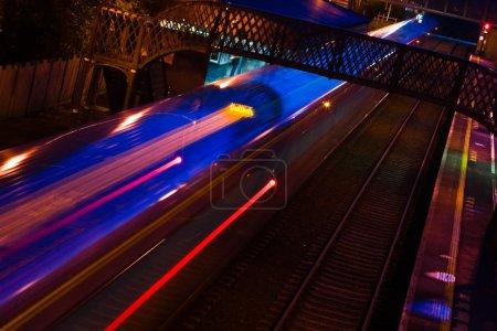 Foto de Tren borroso en movimiento con luces que llegan a la estación por la noche - Imagen libre de derechos