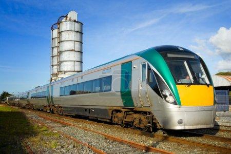 Photo pour Train de voyageurs moderne en mouvement et vieux réservoirs de carburant sur fond - image libre de droit