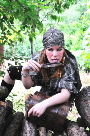 Photo for Beautiful redheaded pirate girl is licking knife - Royalty Free Image