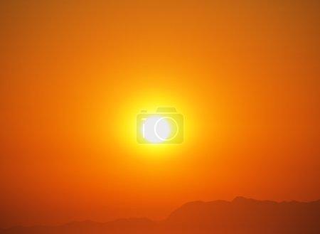Photo pour Coucher de soleil d'été chaud à ciel clair et forme de terre lointaine . - image libre de droit