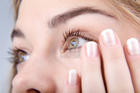 Photo for Opened green eyes and fingernails with french manicure close-up - Royalty Free Image