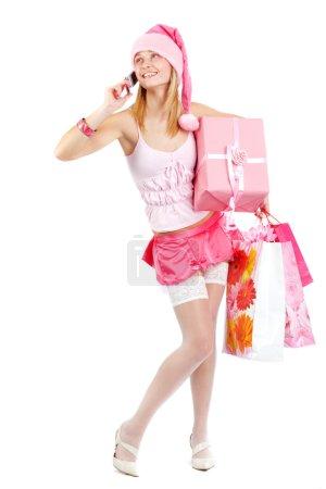 Photo pour Sexy miss Santa tenant des cadeaux et appelant par téléphone isolé sur blanc - image libre de droit