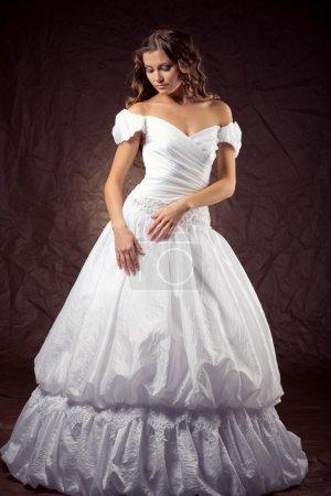 Photo pour Mannequin portant la robe de mariée à fond brun studio - image libre de droit