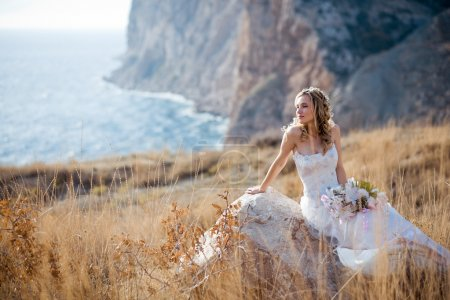 Photo for Beautiful bride sitting on stone at field over mountains and sea coast landscape - Royalty Free Image