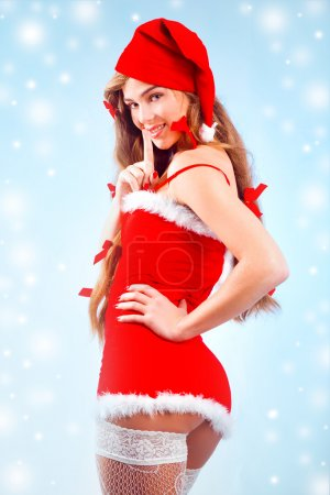 Photo pour Sexy Mme Santa souriant et posant sur fond bleu hiver avec des flocons de neige - image libre de droit