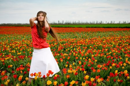 Photo for Young nice girl standing in red and orange tulips field - Royalty Free Image