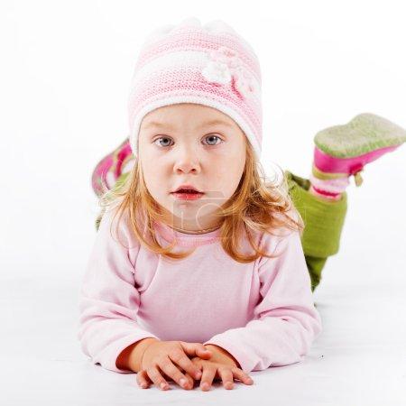 Photo pour Jolie enfant couché et regardant la caméra sur fond blanc - image libre de droit