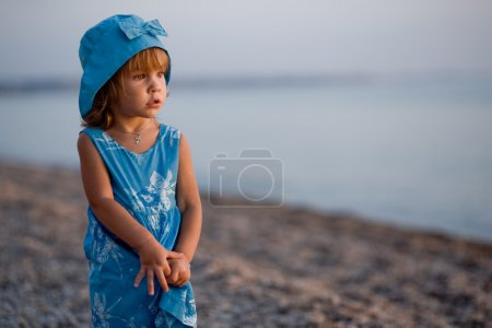 Photo for Baby girl in blue dress and hat staying at beach alone and looking into sea - Royalty Free Image