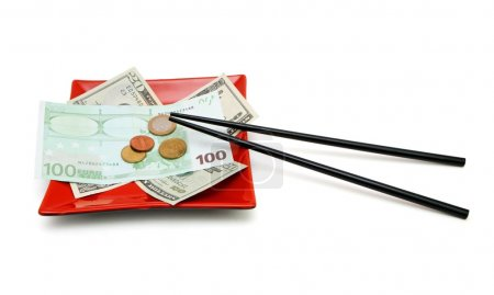 Photo for Money bills and coins on red square plate with chopsticks isolated - Royalty Free Image
