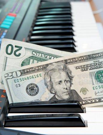 Photo pour Deux billets de vingt dollars coincés dans le clavier de l'orgue électrique - image libre de droit
