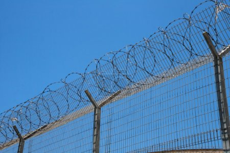 Photo for Fence with spiral barbed wire on top on sky background - Royalty Free Image
