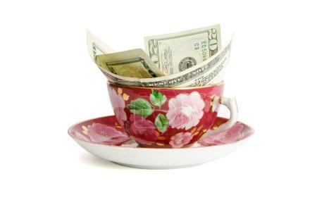 Tea cup with twenty dollar bills