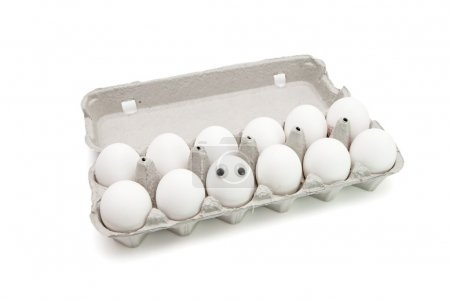 Photo for Funny egg with eyes among dozen in a paper box on white background - Royalty Free Image