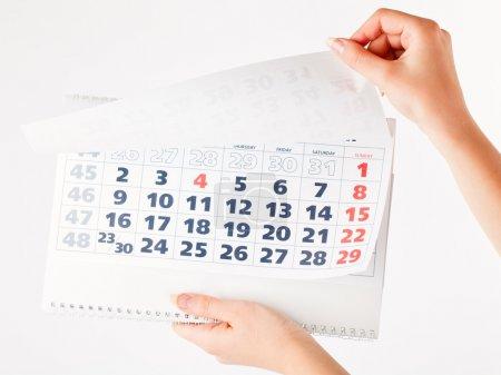 Photo pour Gros plan du calendrier entre les mains. Isolé sur fond blanc - image libre de droit
