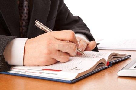 Businessman hands writing in organizer
