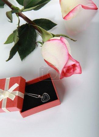 Photo pour Rose et cadeau avec décoration de bijoux sur table miroir - image libre de droit