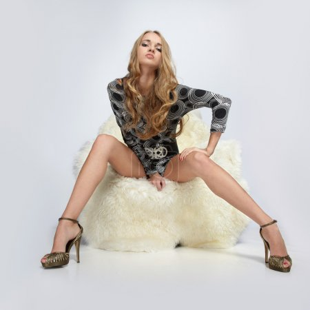 Photo for Portrait of beautiful blonde blue-eyed girl sitting in big furry arm-chair - Royalty Free Image