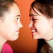 Two funny young girls look at each other...