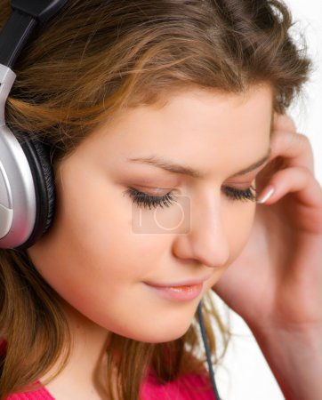 Beautiful young girl listens to music with headpho...