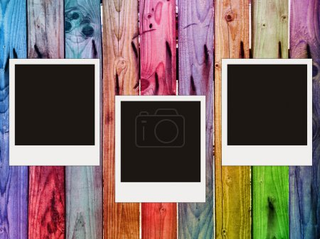 Colorful wooden fence with three blank photos...
